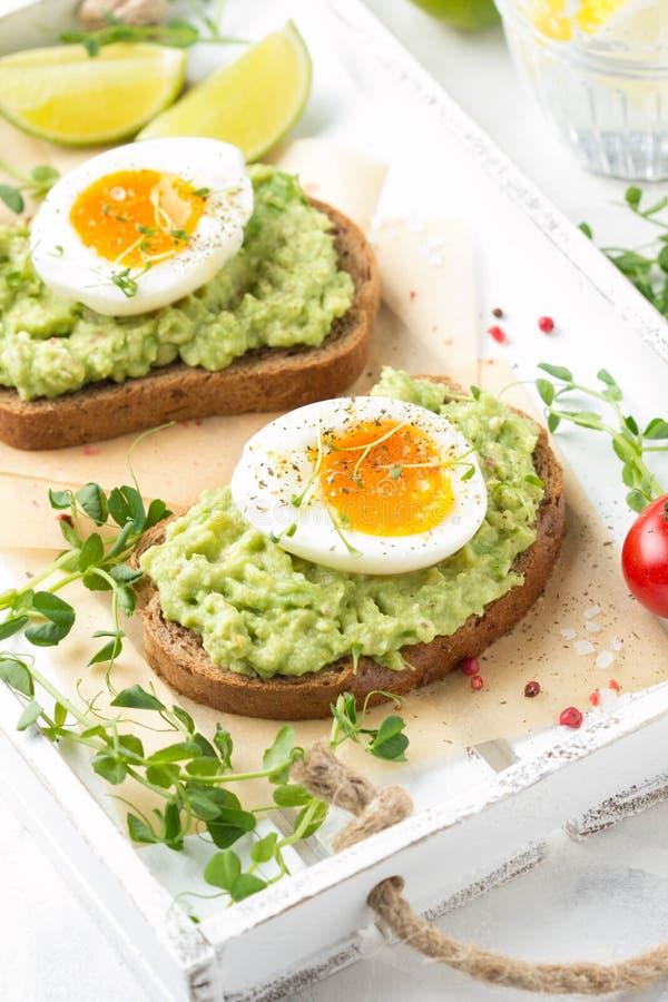 Tostada con pur? del aguacate y el huevo pasado por agua en la bandeja blanca, yema de huevo l?quida, desayuno delicioso, bocadil foto de archivo