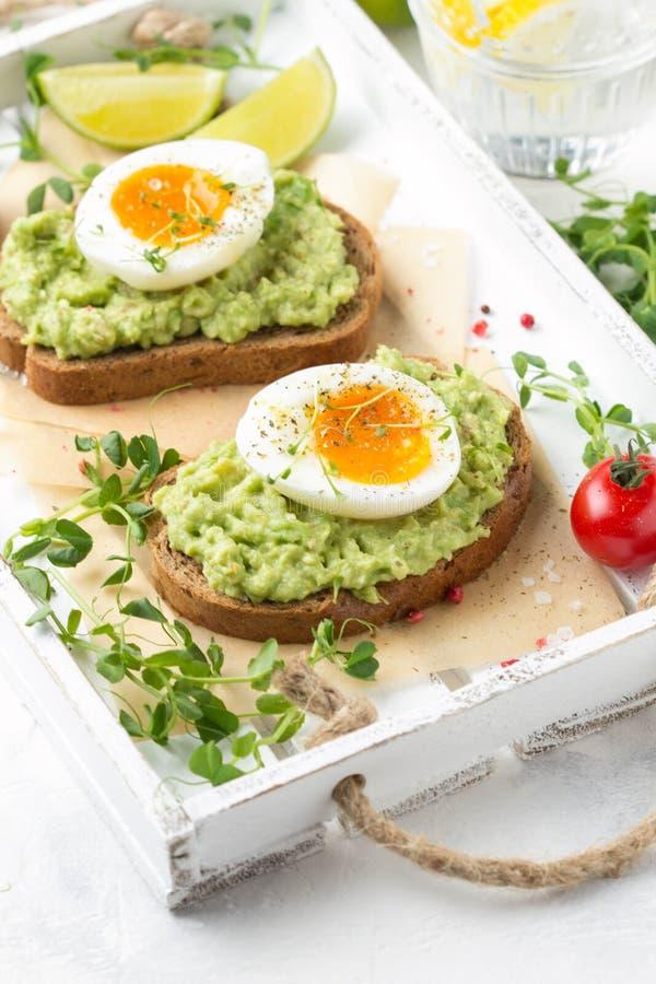 Tostada con pur? del aguacate y el huevo pasado por agua en la bandeja blanca, yema de huevo l?quida, desayuno delicioso, bocadil fotos de archivo
