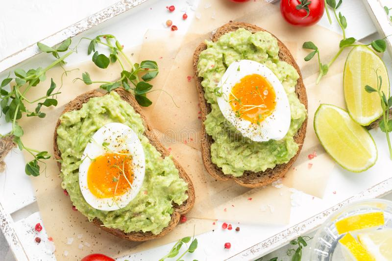 Tostada con pur? del aguacate y el huevo pasado por agua en la bandeja blanca, yema de huevo l?quida, desayuno delicioso, bocadil imagen de archivo