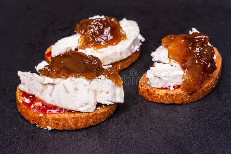 Tostada con queso de cabra y la cebolla caramelizada en pizarra negra imagen de archivo