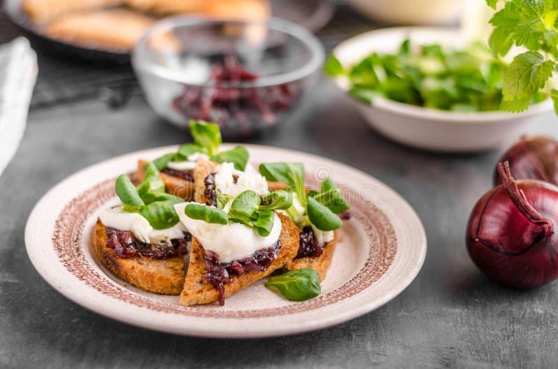 Tostada de la comida de Heatly con la cebolla y la mozzarella imagenes de archivo