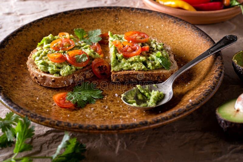 Tostada del aguacate con el tomate y el cilantro cortados imagen de archivo