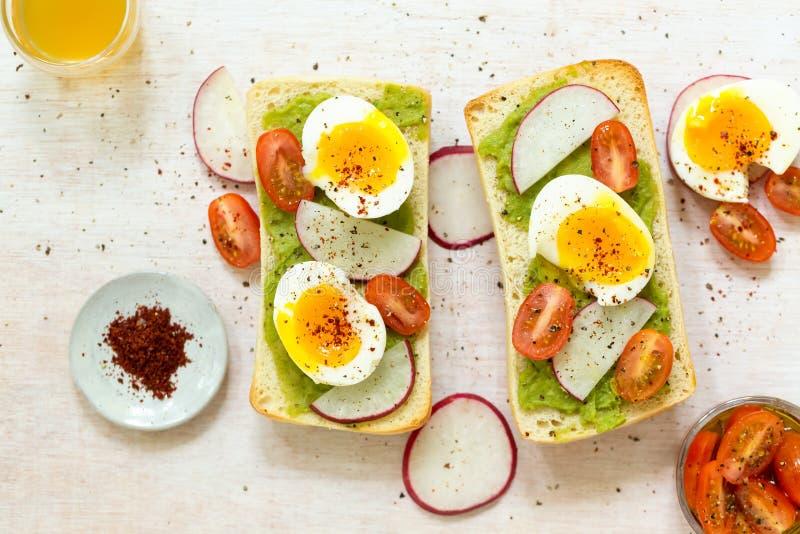 Tostada del aguacate con los huevos y los tomates foto de archivo