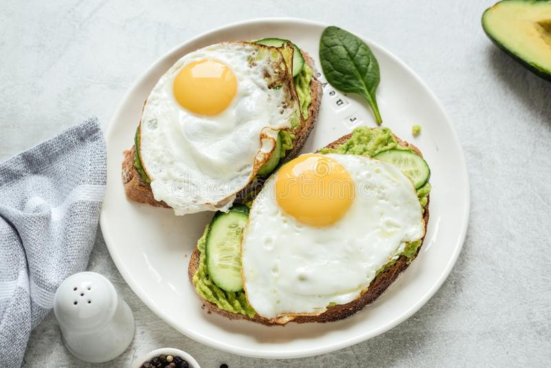 Tostada del desayuno con el huevo frito, el aguacate y el pepino con pan entero del grano en la placa blanca fotos de archivo