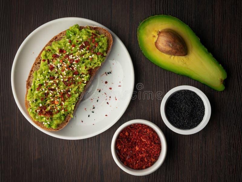 Tostada del pan de pan amargo y pulpa tajada del aguacate con pimienta negra del sésamo y de chile fotografía de archivo