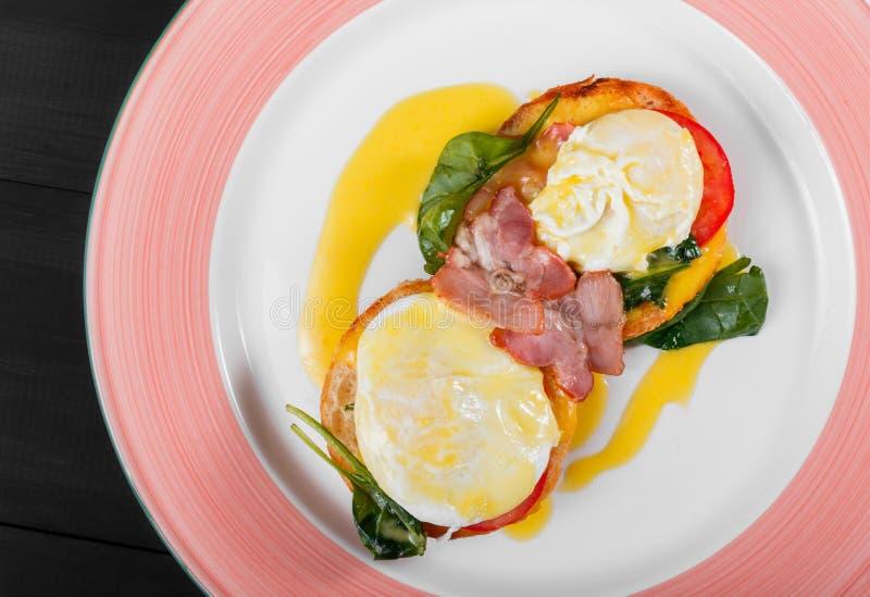 Tostada del pan frito del desayuno inglés con el huevo, la espinaca, los tomates, el queso de la mozzarella y el jamón en la plac fotografía de archivo