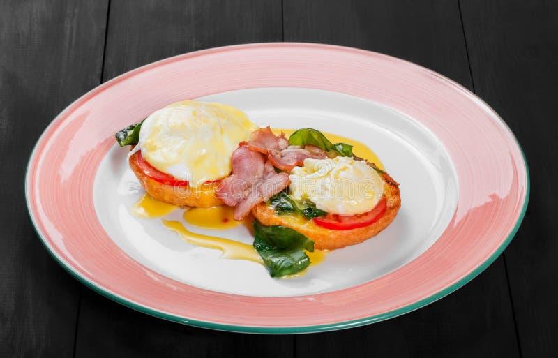 Tostada del pan frito del desayuno inglés con el huevo, la espinaca, los tomates, el queso de la mozzarella y el jamón en la plac fotografía de archivo libre de regalías