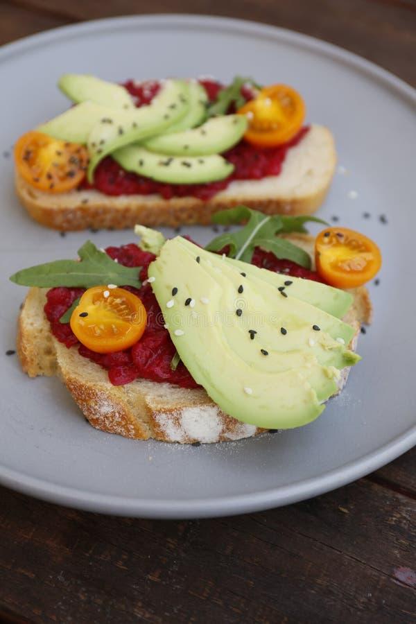 Tostada del vegano con los tomates y las remolachas del arugula del aguacate foto de archivo