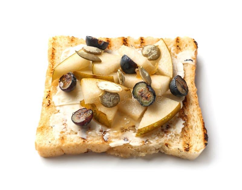 Tostada dulce sabrosa con la pera, las semillas y las bayas cortadas frescas en el fondo blanco fotografía de archivo libre de regalías