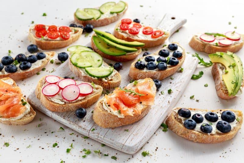 Tostada hecha en casa del verano con la ensalada del salmón ahumado, de los arándanos, del rábano, del pepino, del aguacate y del fotos de archivo