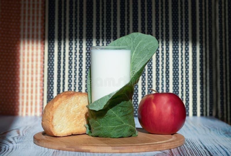 Tostada, leche en un vidrio y una manzana en una bandeja de bambú Ecoproducts para la nutrición dietética y sana imágenes de archivo libres de regalías