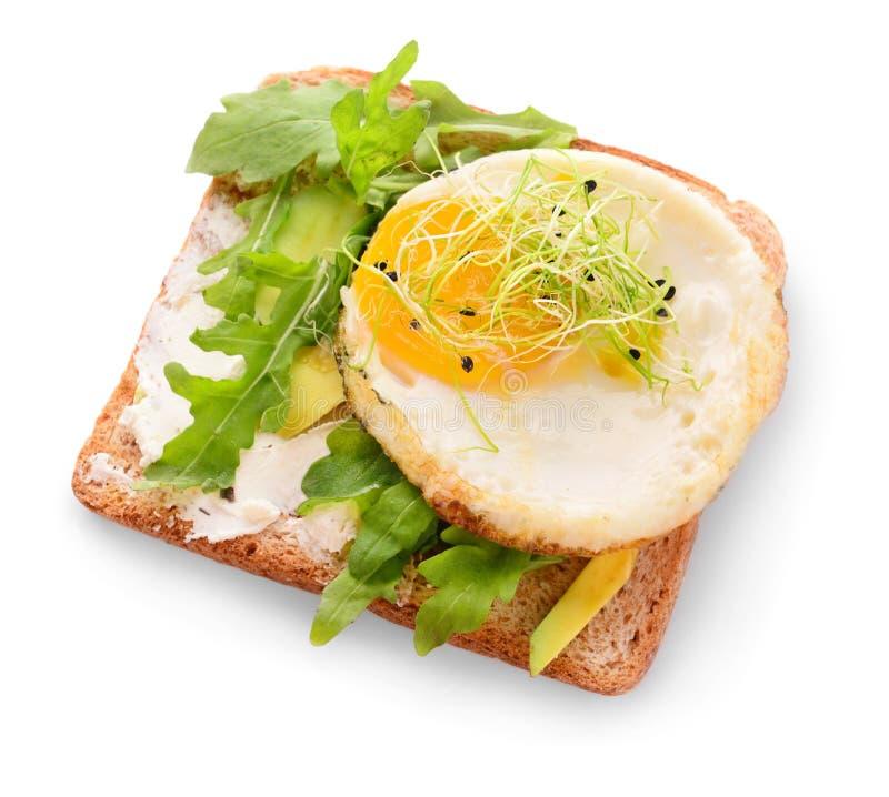 Tostada sabrosa con el aguacate, el huevo frito y el arugula en el fondo blanco fotografía de archivo libre de regalías