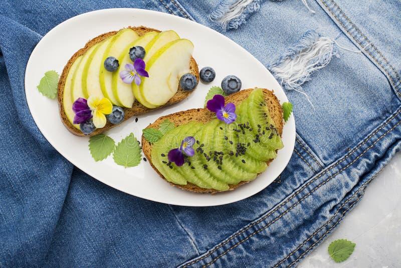 Tostada sana con la manzana verde y kiwi jugoso con las flores comestibles de las violas del jardín en un fondo de mármol Año del imagen de archivo