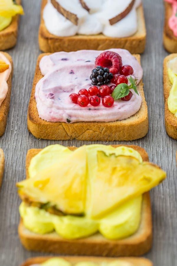 Tostadas clasificadas con las frutas y las bayas en la crema wipped en un tablero de madera en fondo ligero Hecho en casa tradici foto de archivo libre de regalías