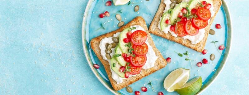 Tostadas con el queso feta, los tomates, el aguacate, la granada, las semillas de calabaza y los brotes de la linaza Desayuno de  imagen de archivo libre de regalías