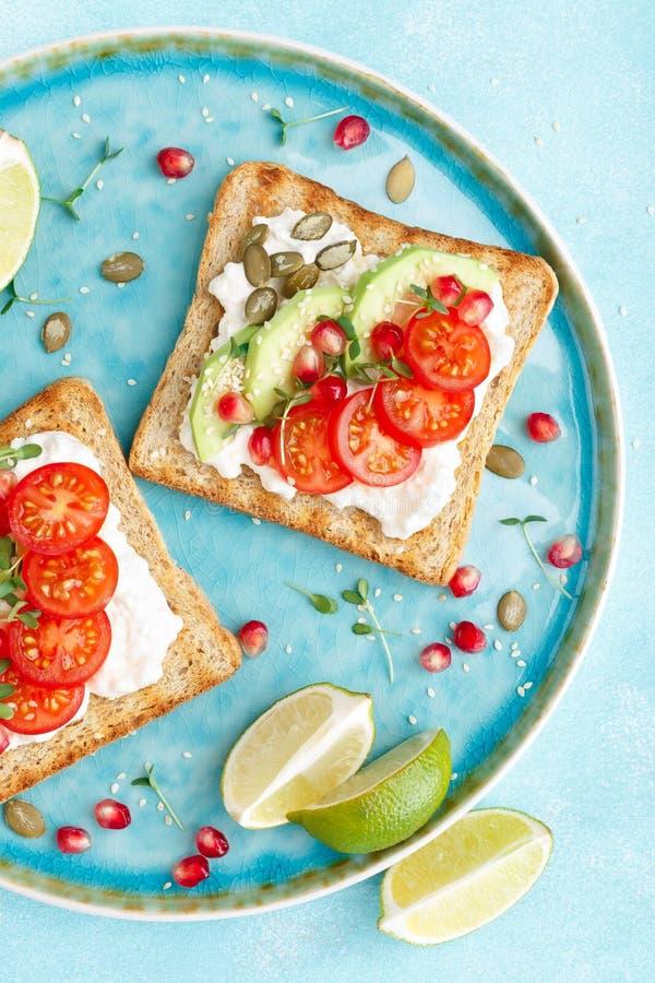Tostadas con el queso feta, los tomates, el aguacate, la granada, las semillas de calabaza y los brotes de la linaza Desayuno de  imagenes de archivo