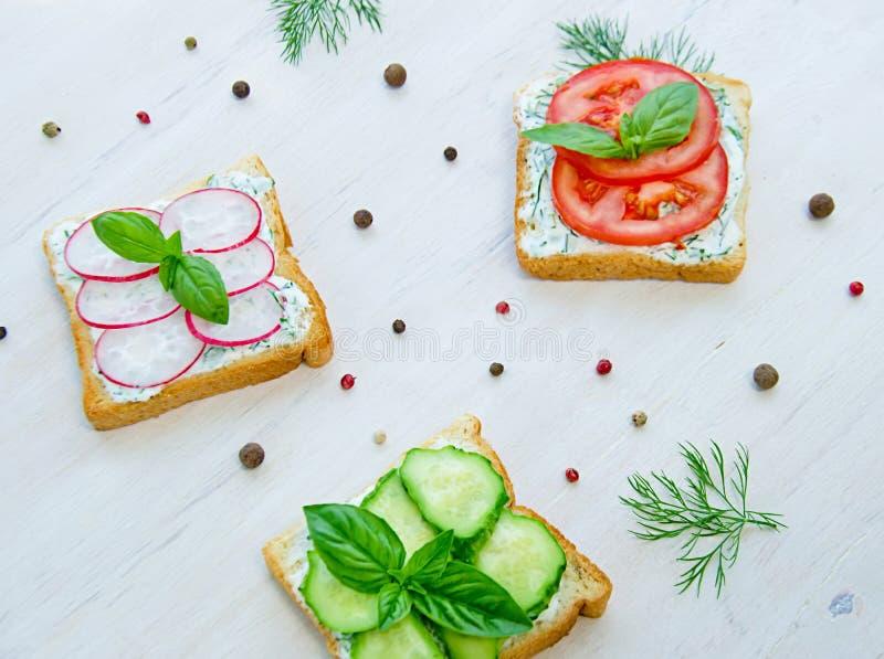 Tostadas con el tomate tajado y el pepino verdes del rábano adornados con albahaca en un fondo de madera al lado de los guisantes fotos de archivo libres de regalías
