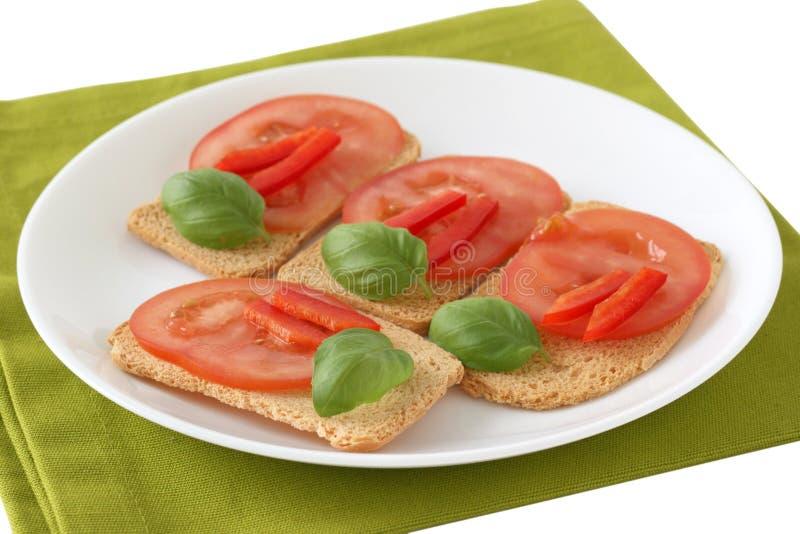 Tostadas con el tomate y la albahaca imagen de archivo libre de regalías