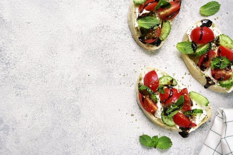 Tostadas con queso Feta, el tomate, el pepino y la menta Visión superior con el espacio FO imágenes de archivo libres de regalías