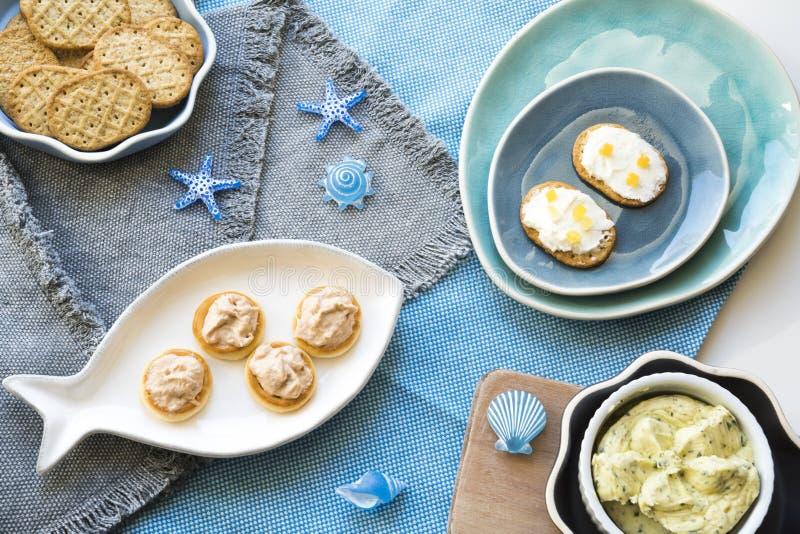 Tostadas curruscantes en varias placas azules, con el atún y ensalada, queso cremoso y mantequilla de color salmón fotografía de archivo libre de regalías