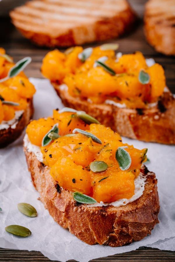 Tostadas del queso de la calabaza y de cabra con las semillas del sabio y de calabaza fotografía de archivo