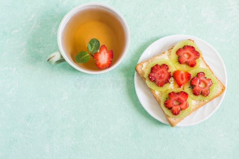 Tosti con formaggio cremoso, il kiwi e le fragole nella forma di fiore immagini stock