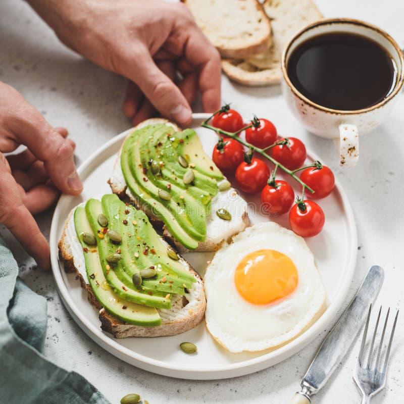 Tosti con l'avocado, l'uovo fritto, i pomodori e la tazza di caffè Prima colazione sana fotografie stock libere da diritti