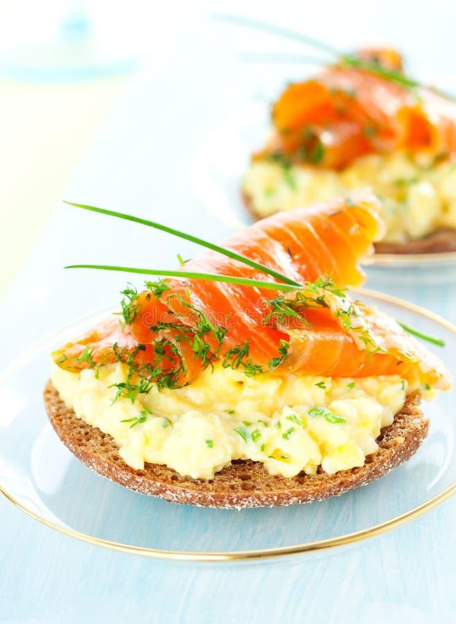 Tosti con le uova, i salmoni e la erba cipollina rimescolati fotografie stock
