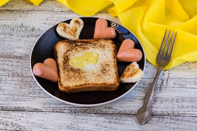 Tosti con le uova rimescolate si formano dei cuori, salsiccie fotografie stock libere da diritti
