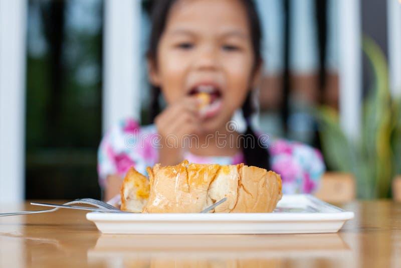 Tosti con sciroppo dolce sul piatto con il cibo asiatico della ragazza del bambino fotografie stock