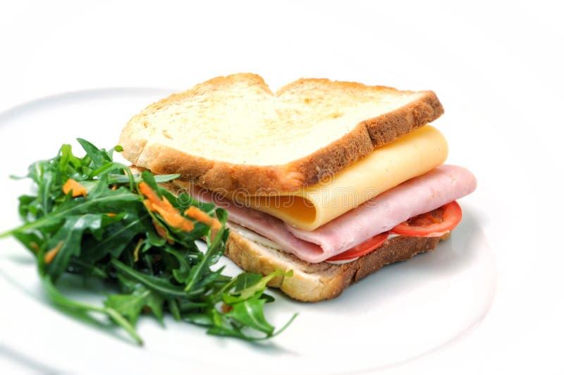 Tosti il panino con il prosciutto, il formaggio, i pomodori e l'insalata sul piatto bianco, su fondo bianco immagine stock libera da diritti