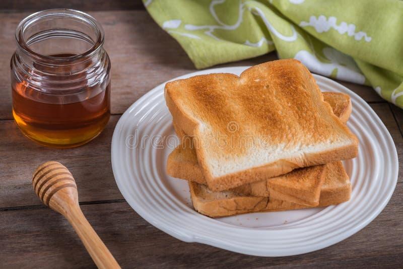 Tosti sul piatto e sul miele in barattolo di vetro immagine stock