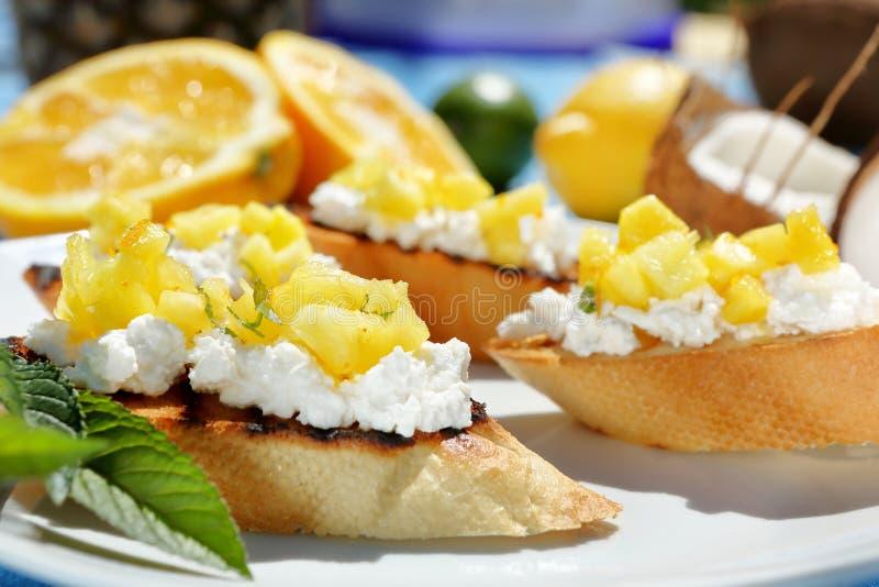 Tosts用酸奶干酪和菠萝在板材 免版税库存图片