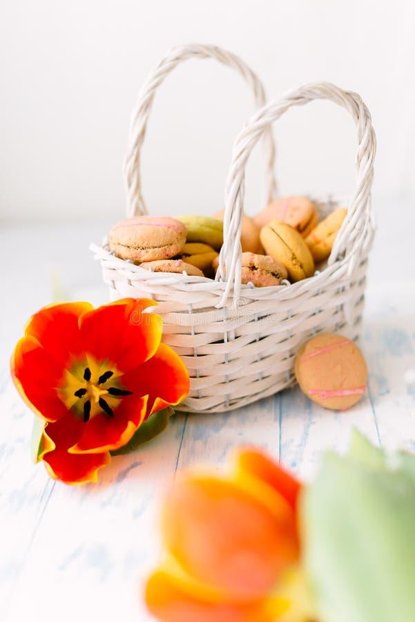 Tot bloei komende tulpen met makarons op een lichte houten achtergrond Stilleven, de lenteconcept royalty-vrije stock fotografie