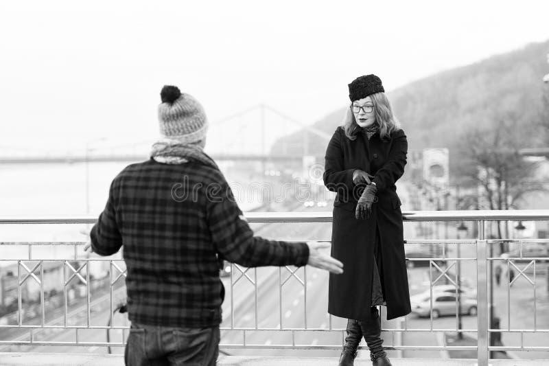 Tot op heden vertraagde kerel De vrouw toont tijden op wapen De mens spreidde van hem uit uitdeelt op brug en het lopen gebied stock fotografie