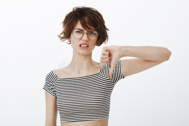Totaal afkeer nieuwe film Portret die van ontstemde en teleurgestelde mooie vrouw met kort slordig haar, fronsen en stock foto