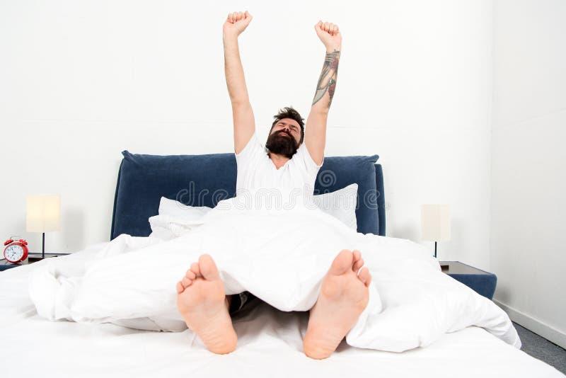 Totaal Ontspannen rijp mannetje met baard in pyjama op bed brutale slaperige mens in slaapkamer in slaap en wakker energie en stock afbeelding