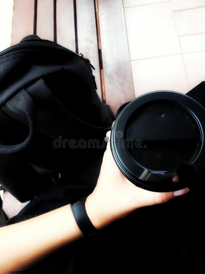 Total black style. Bag, smartwatch and coffee cup in female hands. Soft Light. Wooden. Classic style. Fashion royalty free stock photos