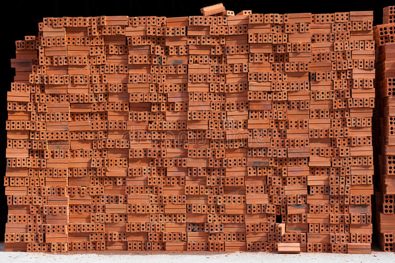 Total block of irregularly stacked building red bricks. On black background stock image