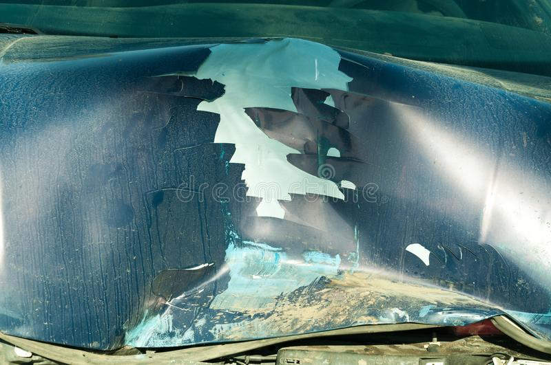 Total damage on the blue car hood with broken metal parts scratched paint and rusty dirt from cooler destroyed in crash accident c royalty free stock photos