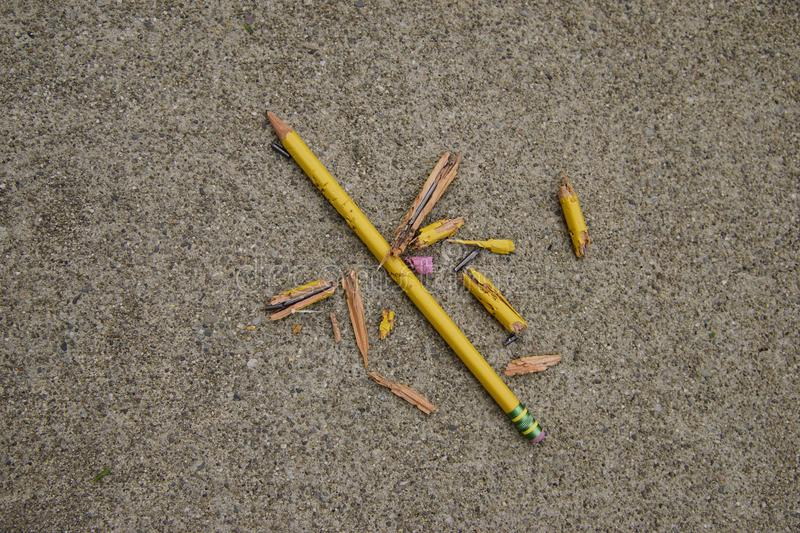 Total Destruction of a Pencil. Two yellow pencils on a gray concrete one in many pieces the other still whole with bite marks, chewed up by a dog royalty free stock photos