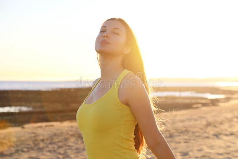 Total relax. Free happy woman enjoying breathing at sunset on the beach. Young woman relaxing in summer sunset sky outdoor. People. Freedom style stock photos