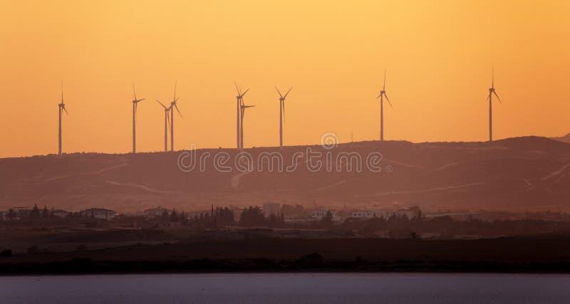 Total- sikt av vindkraftgeneratorer på bakgrunden av sunse arkivbild