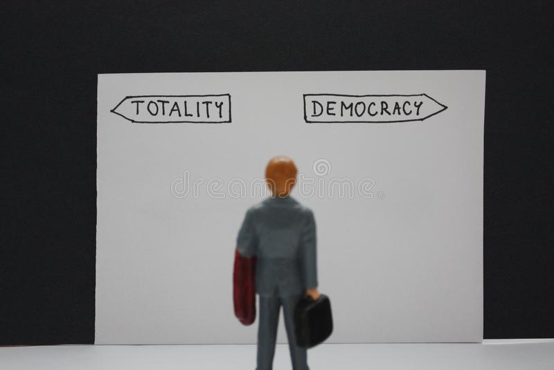 A totalidade contra opções da democracia com opções do guidepost dois das setas e pouco homem decide sobre ela, a liberdade ou a  foto de stock royalty free