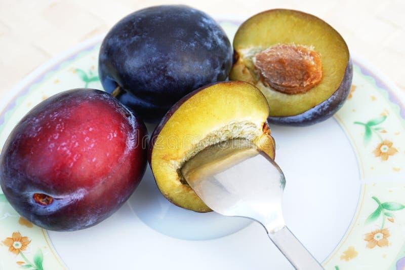 Totalité et demi prunes naturelles mûres, fruit sur la table de thé avec la cuillère au milieu images libres de droits