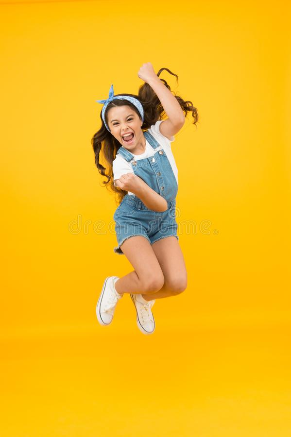 Totally happy. Energy inside. Feeling free. Summer holidays. Jump of happiness. Small girl jump yellow background. Enjoy. Freedom. Childrens day concept. Spirit royalty free stock photos
