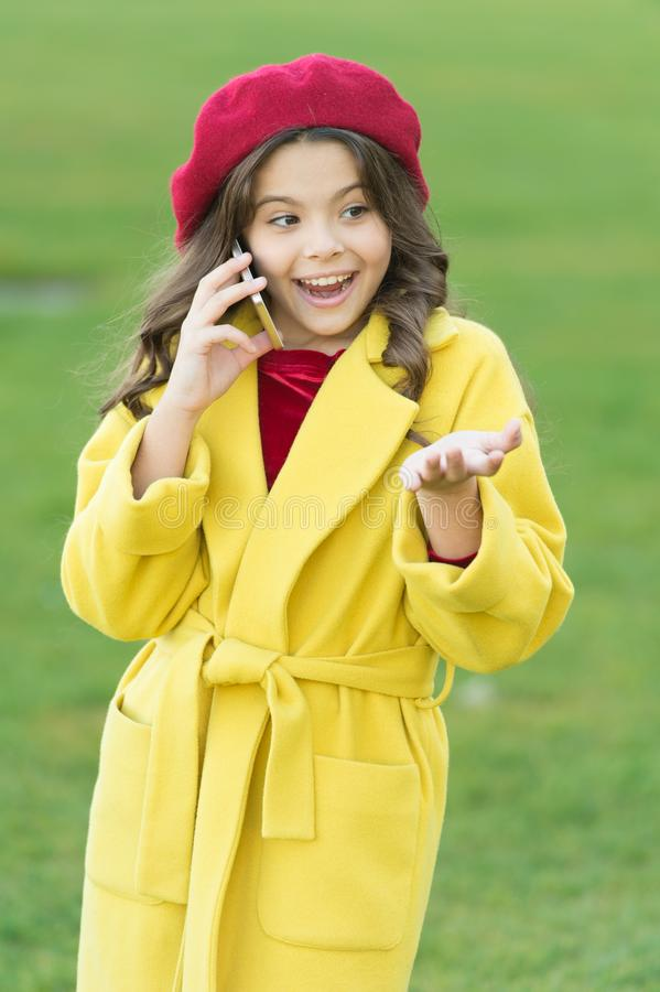 Totally happy. fall season. happy childhood. small child with phone. beauty in autumn coat. cheerful little girl in royalty free stock photo