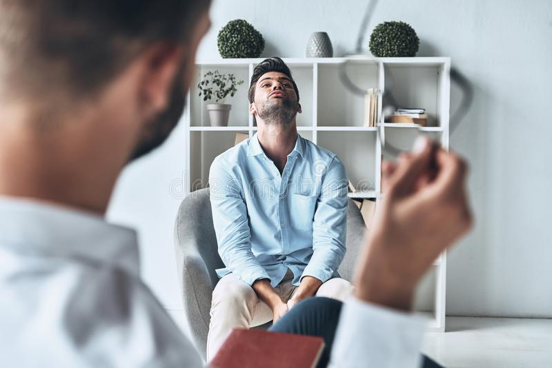 Totally lost. Young frustrated men solving his mental problems while having therapy session with psychologist royalty free stock photo