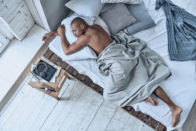 Totalt avkopplat Bästa sikt av den unga afrikanska mannen som sover medan ly arkivfoton