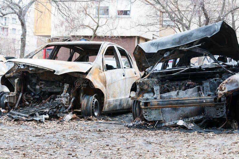 Totalt förstörda bilar brände i brand i krigzonen eller i nära övre för borgerliga demonstrationer royaltyfri foto